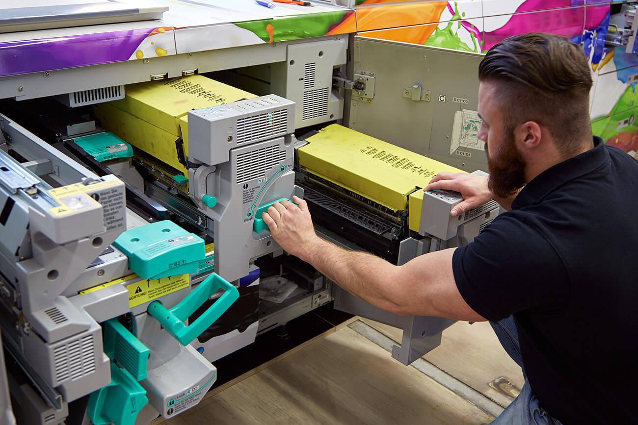 Ein Papierstau wird aus der großen Druckmashcine entfernt, dann geht es gleich weiter mit der Produktion