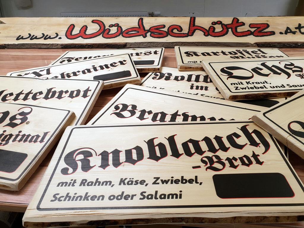 Holzplatten bedruckt mit rot und schwarzem Schriftzug