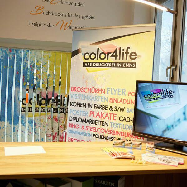 Im Eingangsbereich der color4life steht ein Rollup mit allen Produkten und ein Imagevideo unserer Produktionshallen wird vorgeführt