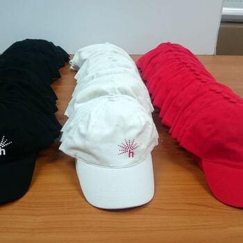 Auch Kappen werden mit einem Logo bedruckt. Hier in Schwarz, Weiss und Rot