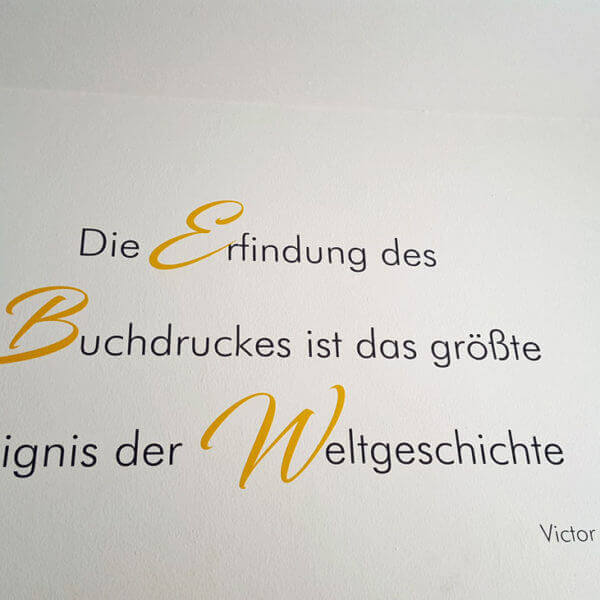 Klebeschrift in Gelb auf weisser Wand