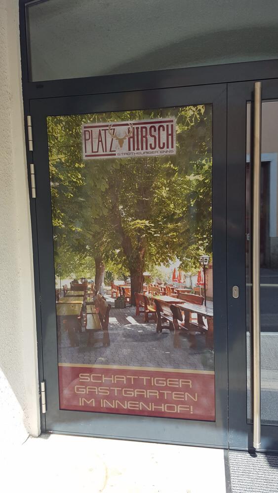 Schattiger Gastgarten - Eingangstüre mit Lochfolie beklebt bei Platz-Hirsch in Enns