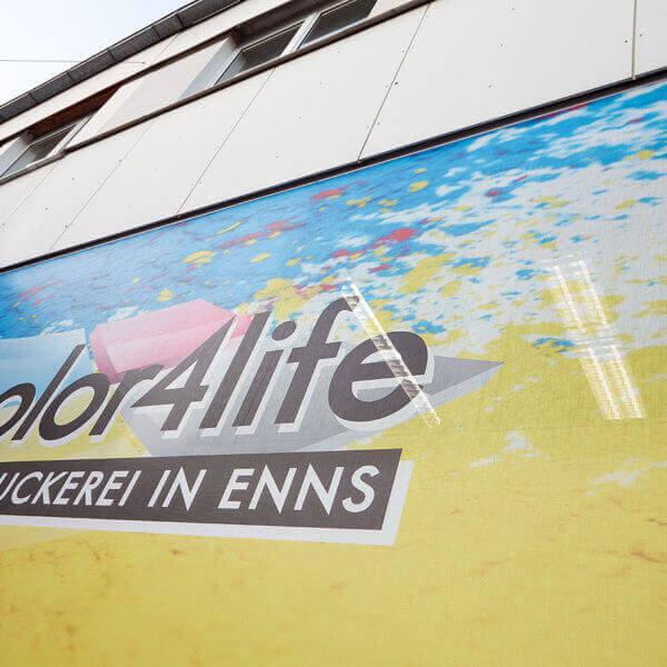 die Logobespannung der Fassade ist in gelb gehalten und in den Firmenfarben