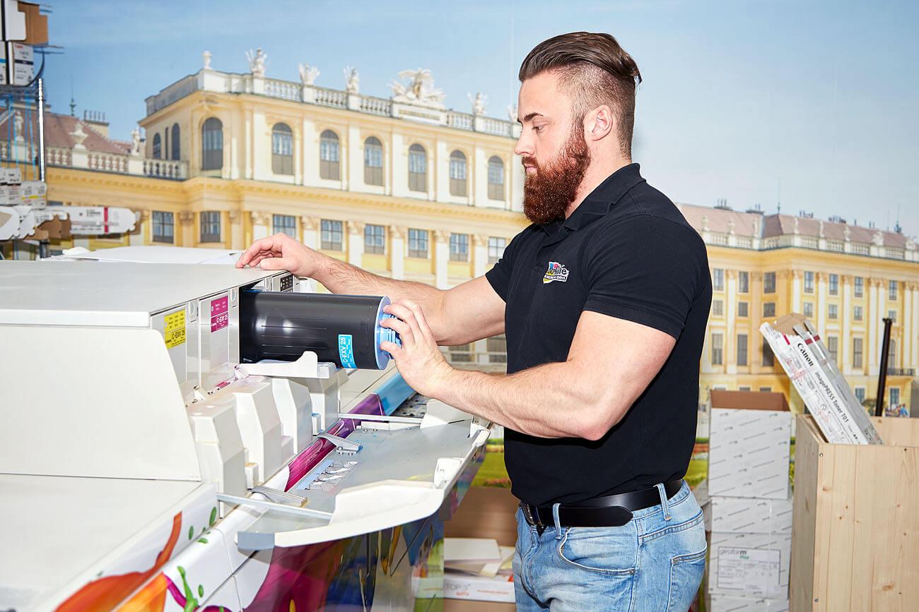 Herr Frattner wechselt den leeren Toner bei der Canon Druckerei