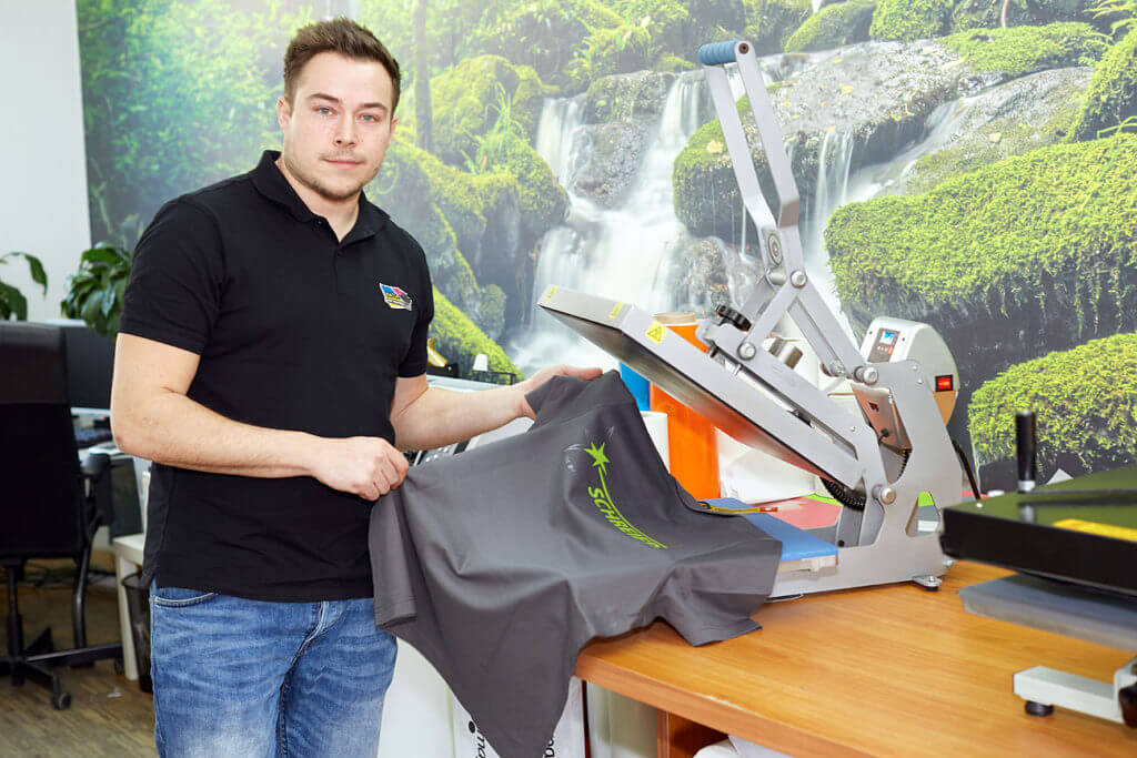 Fertig: zufriden zeigt Herr Ernst das fertige T-Shirt in die Kammera