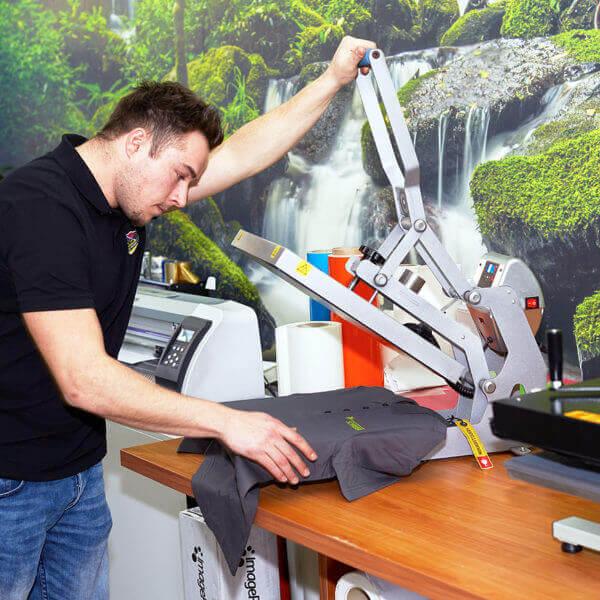 Herr Ernst bei der T-Shirt Presse um ein Logo aufzudrucken